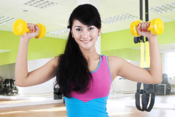 Female trainer exercising with dumbbells