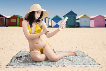 Girl using sunscreen with beach background