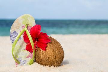 Kokosnuss, Hibiskusblüte und Flip Flops am Strand