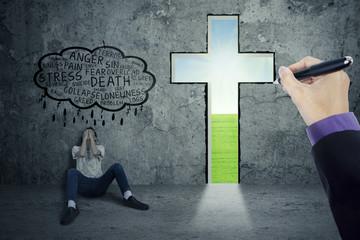 Stressful person sitting near a cross