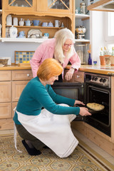 Mom Watching Other Mom Putting cake in an Oven.