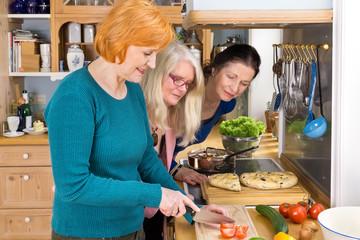Moms Looking at their Friend Slicing Ingredients.