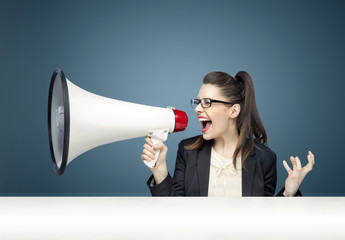 Young businesswoman yelling over megaphone