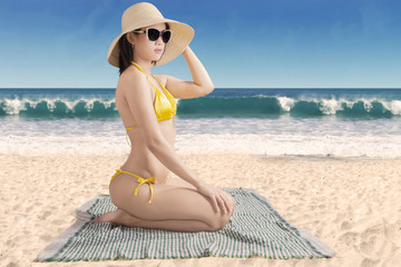 Woman wearing swimwear sitting at seashore