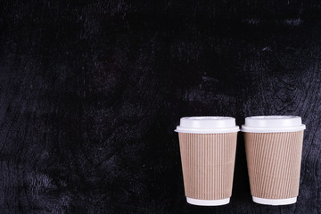 2 paper cups for coffee, tea on a black background.