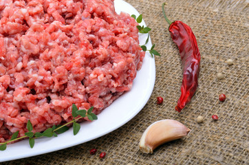 Close-up of minced  meat with pepper,  thyme and garlic