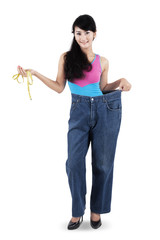 Woman with measurement tape and old jeans