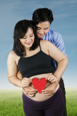 Young parents holding heart symbol