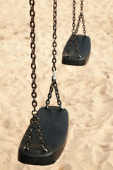 Empty swings made of black plastic and steel chains