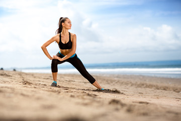 Fit woman  doing exercises for legs on the beach