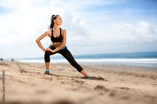 Fit woman  doing exercises for legs on the beach - 81785687