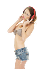Woman in shorts with headphones.