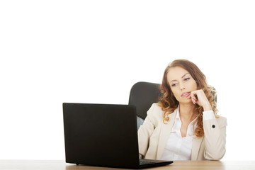 Focused businesswoman working on laptop.