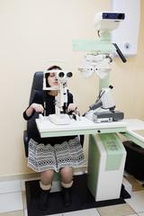 Woman looking into eye test machine
