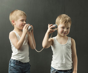 Cute little brothers talking on the toy phone