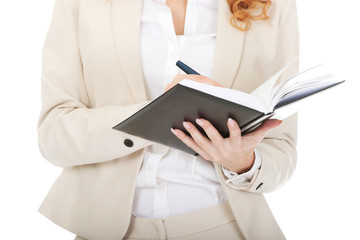 Businesswoman writing in a note.