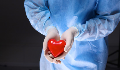 Female doctor with stethoscope holding heart, isolated on white