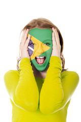 Brazilian flag painted on woman's face.