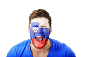 Screaming man with Slovenia flag on face.
