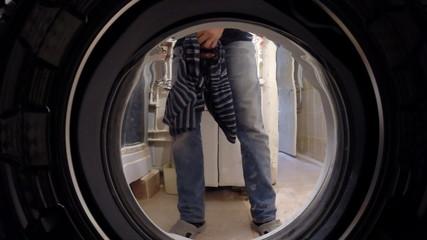 Washing machine inside. Man laying on linen washing
