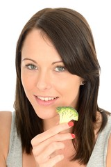 Attractive Healthy Young Woman Eating Broccoli