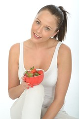 Healthy Young Woman Holding a Bowl of  Ripe Juicy Strawberries