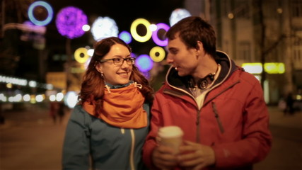 Young happy couple man and attractive girl walking down the