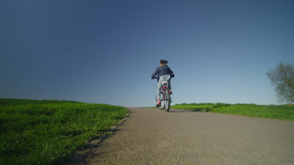 Little child riding a bike into the distance on a path
