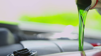 Close up of fresh oil pouring into a car engine