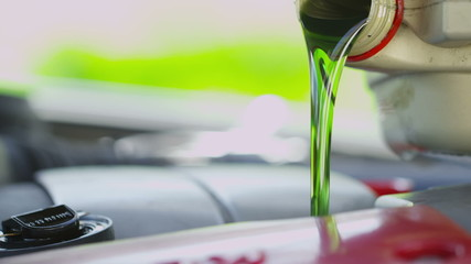 Oil being poured into a car engine in slow motion