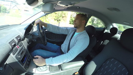 Interior view of man driving a car in the daytime