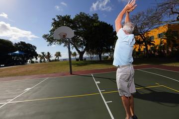 Stock image old man playing basketball