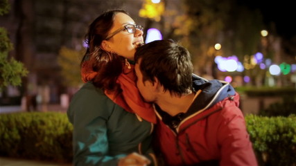Young couple cuddling on date in night city. Attractive girl