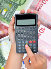 hands with calculator against the background of euro banknotes