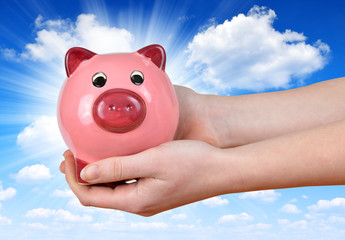 Woman hand holding a pink piggy bank