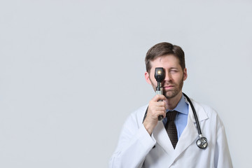 Physician looking through ophthalmoscope