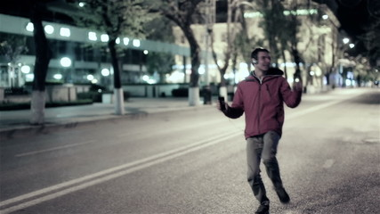Funny guy walk down the night street city, free dancing to music