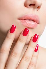 Крупным планом женские губы и рука с красным маникюром.
