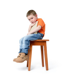 Child sitting on a chair with a book, on white background