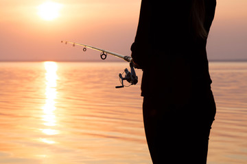 silhouette of a girl on the bank of the river with a fishing rod