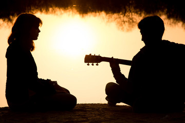 silhouette of a young boy and girl on the beach with a guitar