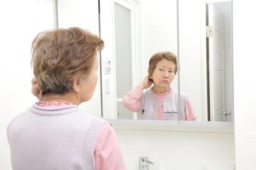 洗面台の鏡の前に立っている一人の高齢者アジア人女性