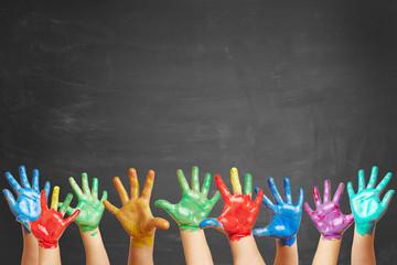 Bunte Kinderhände mit Fingerfarbe vor Tafel