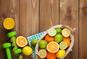 Citrus fruits in basket and dumbells. Oranges, limes and lemons