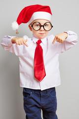 Kind als Weihnachtsmann zeigt mit Fingern