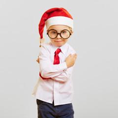 Kind als Weihnachtsmann mit verschränkten Armen