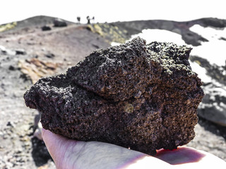 Volcanic rock in human hand at mount Etna, Sicily.