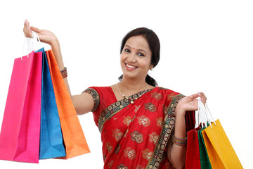 Young traditional Indian woman holding shopping bags