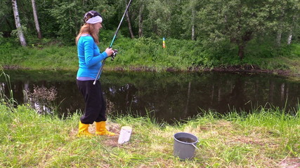 Pregnant woman in yellow boots catch fish and give for cute cat