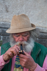 portrait of an old man with a long beard smoking a pipe